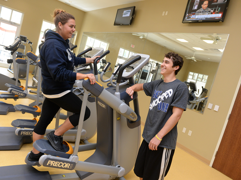 Two residents talking and exercising in the Fountains gym which has several fitness equipment, windows and a few tvs.