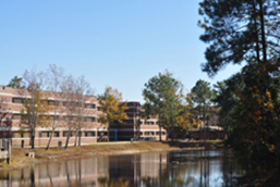 Osprey Hall Preview of tress off to the right and the tan building on the left with a view of a lake in front