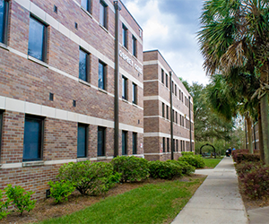 UNF Osprey Cove three story residence hall, tan building with dark brown doors with greenery around