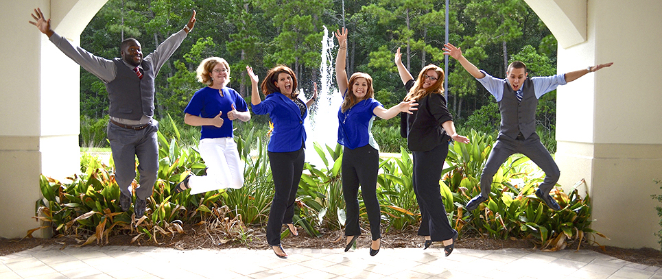 Residence life staff jumping with fun expressions in a student residence area in front of a fountain