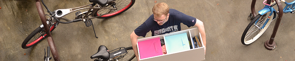 Arial view of a guy student walking through a bike carrying a box filled with resident room accessories
