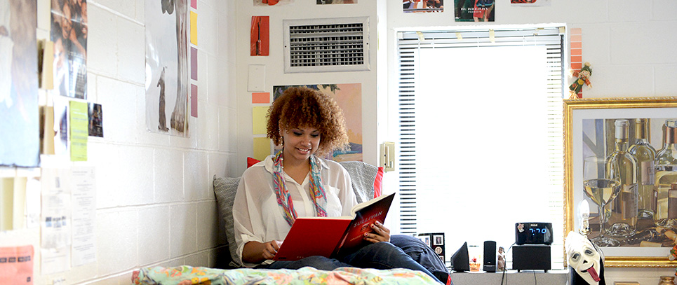 Girl student sitting on her bed in her personalized residence hall reading a text book