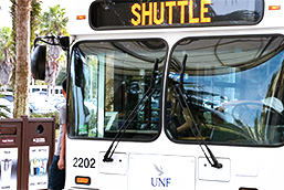 White UNF Shuttle bus at a shuttle stop