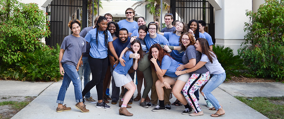 Student Staff members posing together outside a residence hall pointing and smiling and having fun while interacting with the camera
