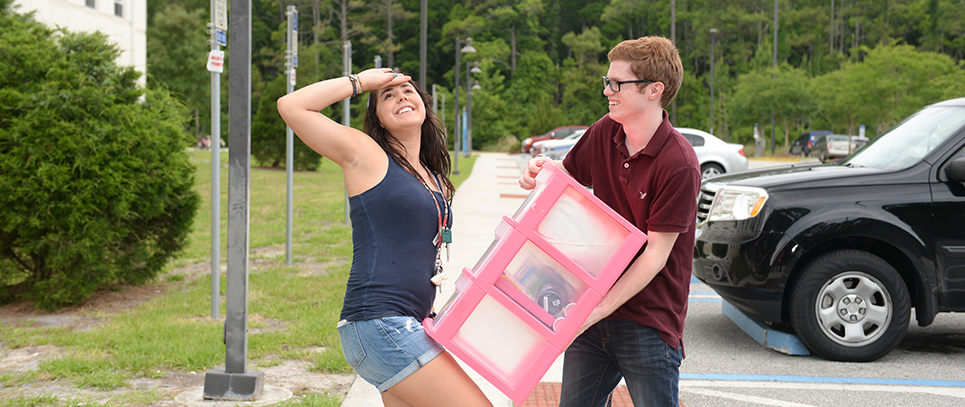 Two students having fun while help each other move items to the residence hall
