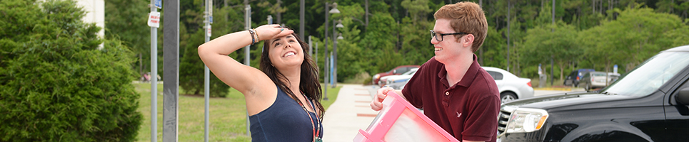 Housing and residence life movie in fun. Guy student assisting a girl student with a storage case