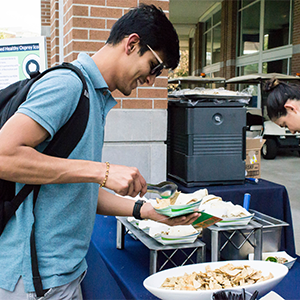 a student making a taco at a UNF dining services event on the green