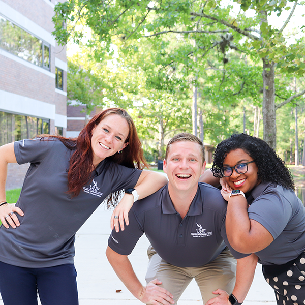Housing and residence life assistant directors outside around beautiful greenery