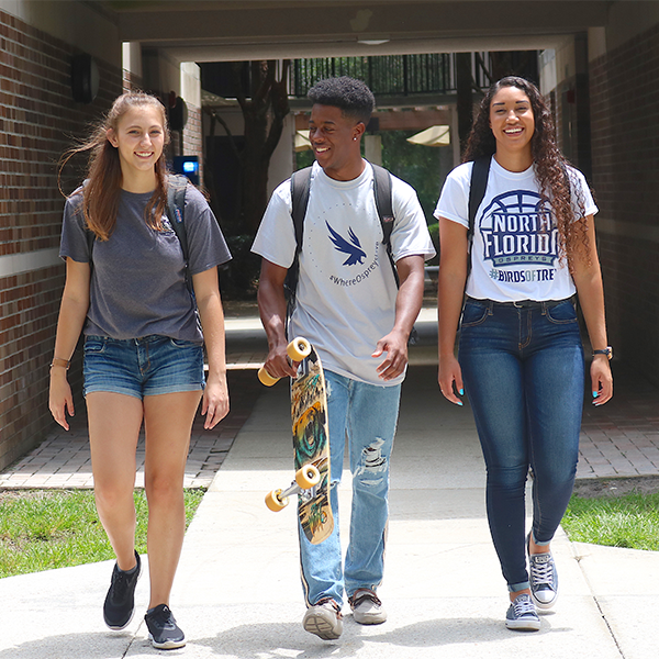 three residents walking and laughing together around the residence halls area
