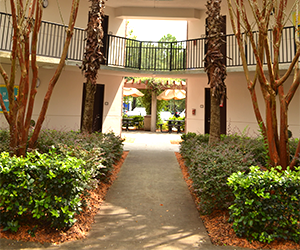 Osprey Cove three story residence hall, tan building with dark brown doors with greenery around