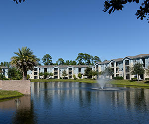 The Flats at UNF Outside with green grass, a lake with a fountain and trees