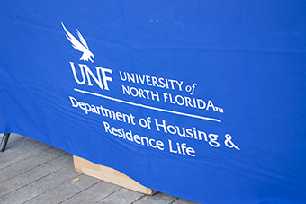 UNF Housing and Residence Life logo on a blue table banner