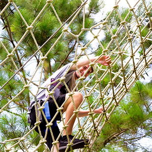 resident enjoying the ropes course at eco adventure LLC retreat