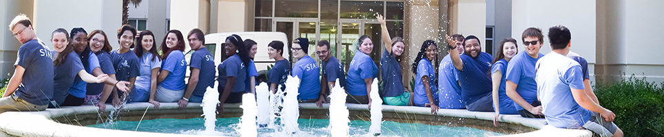UNF student staff sitting together wearing blue Housing and Residence Life staff shirts sitting in front of a waterfountain splashing water and smiling in front of Osprey Fountains residence hall