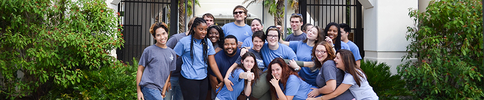 A picture of UNF student staff of all ethnicities posing together outside a residence hall area with fun expressions on their faces and some pointing at the viewer