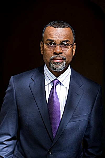 Press photo of Dr. Eddie S Glaude Jr on a dark background. Dr. Glaude wears a navy suit and white dress shirt with purple stripes, and a purple tie. Dr. Glaude wears his glasses in this photo.