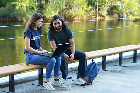 two students sitting on a bench by the lake with a laptop