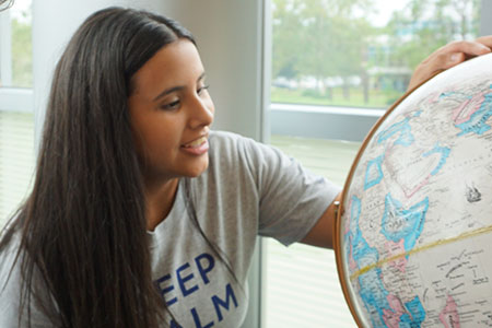FAQ question section picture of a female student pointing at place in a globe