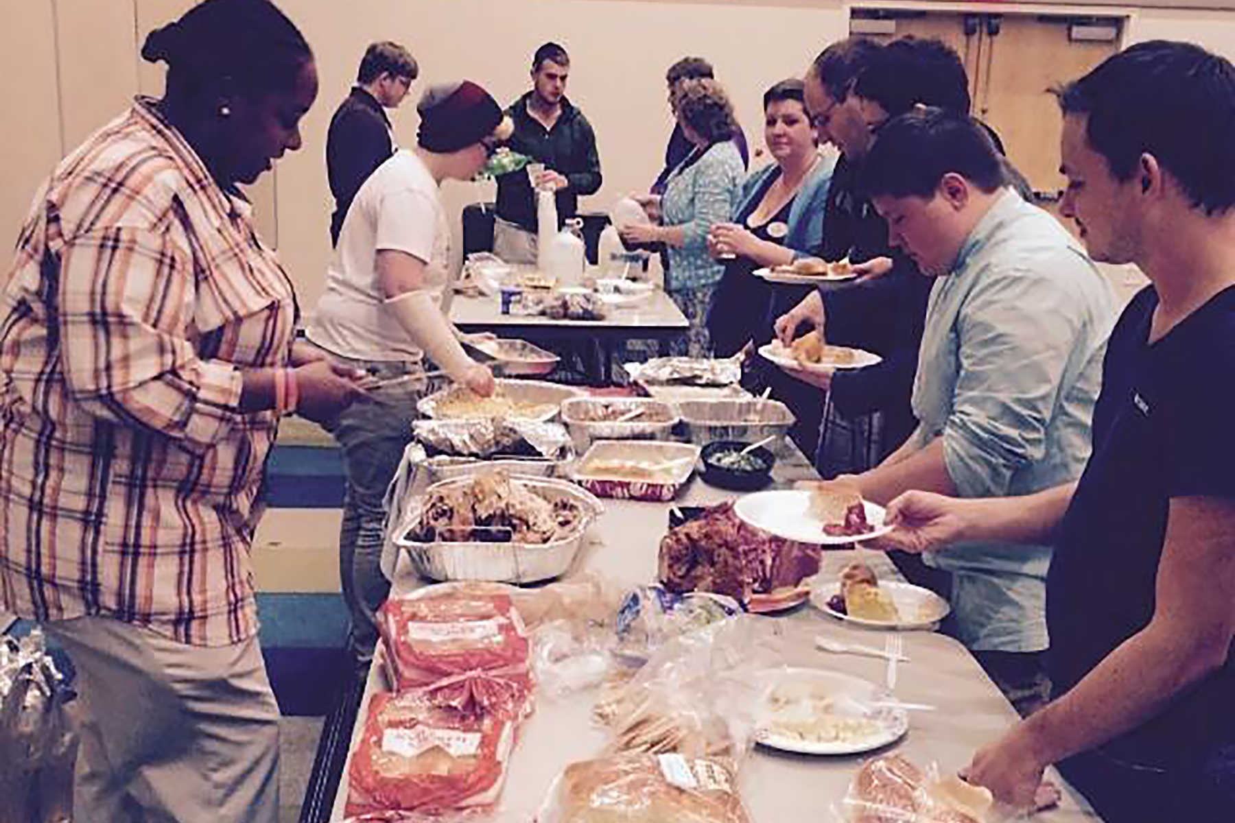 Multiple students are pictured standing around a buffet of food to celebrate the Thanksgiving holiday.