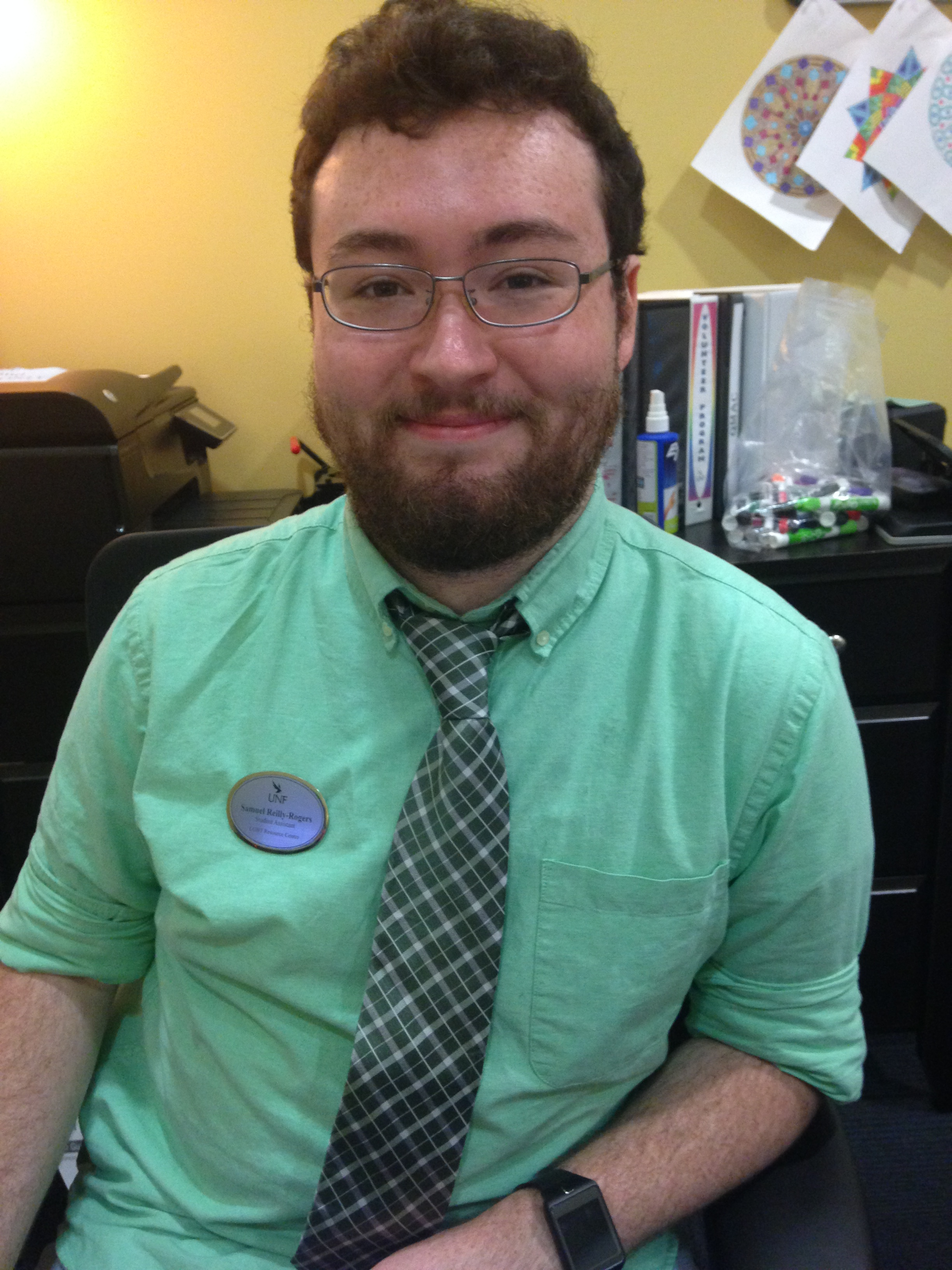 Samuel Reilly-Rogers in a green button-down shirt and a tie at his desk in the LGBT Resource Center