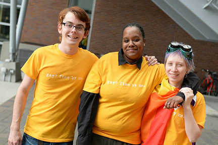Three students are pictured wearing yellow gay fine by me t-shirts