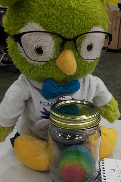 Charlie is wearing glasses and white shirt with blue bowtie, and has a jar with a rainbow brain