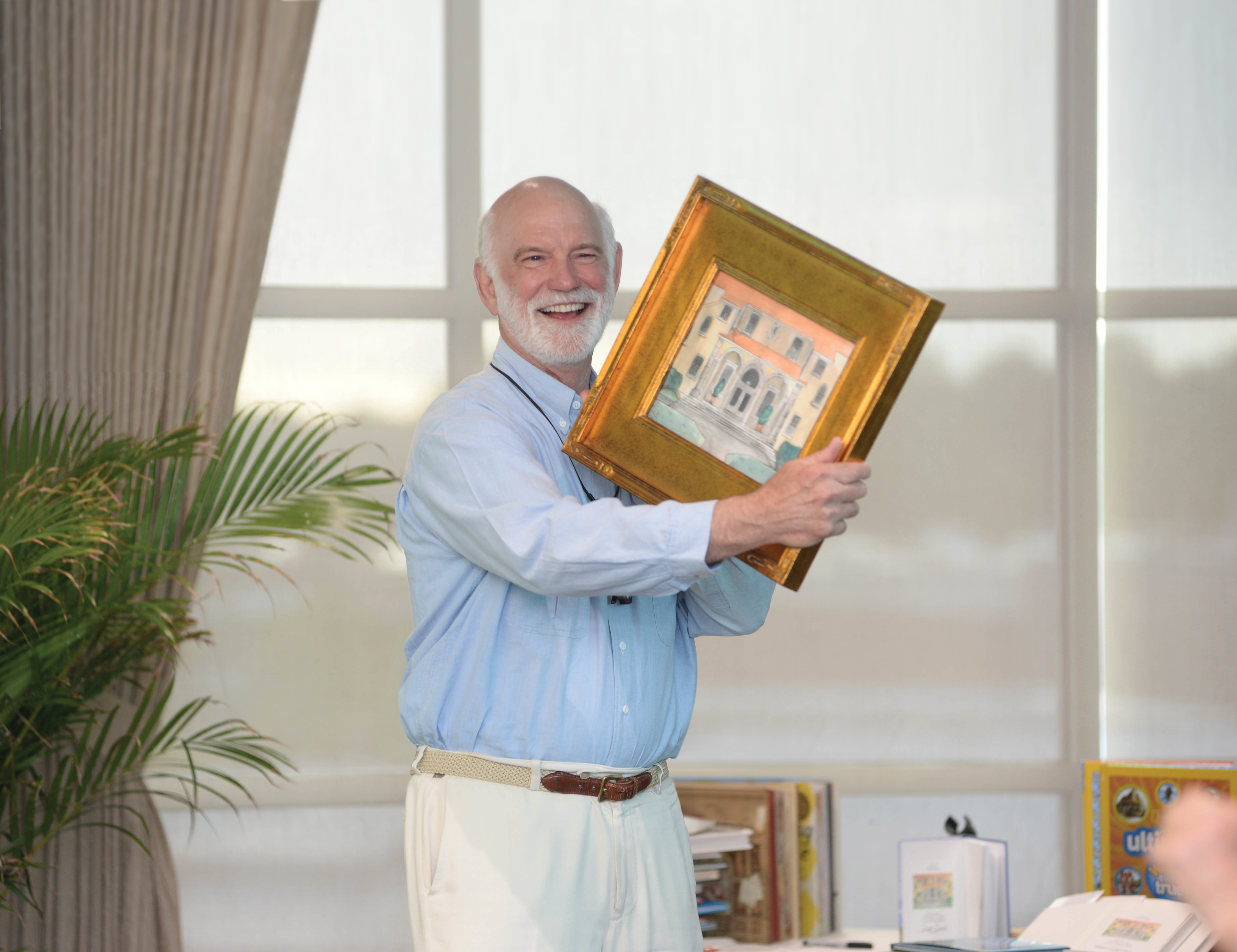 Mr. Berg holds a painting of Orega Elementary school