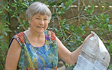 Dr. Lynne Raiser holds her late husband's handmade scroll that tracked their investments.