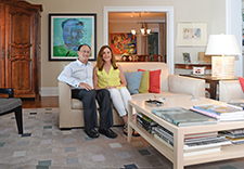 Todd Sack and Barbara Sharp seated on couch in their home with paintings hanging in the background