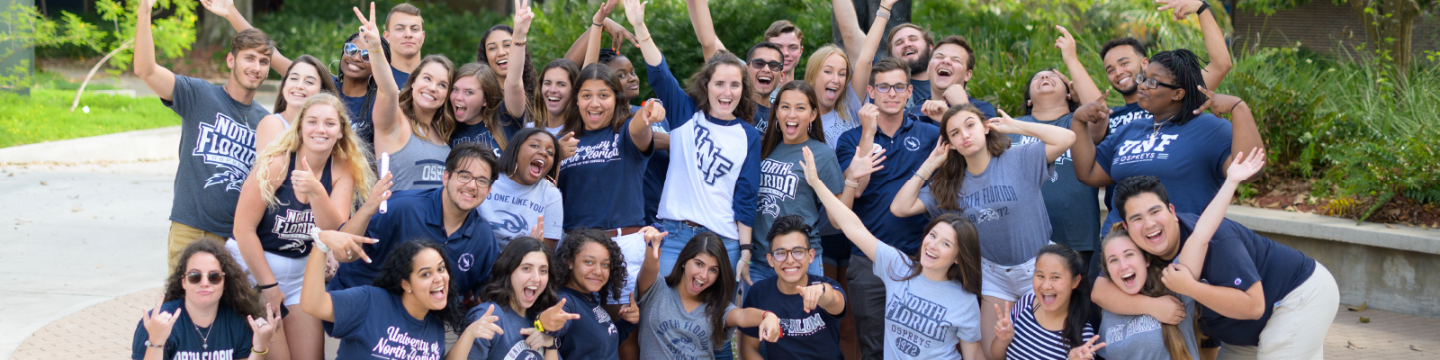 Large group of students in UNF apparel huddled together making silly faces