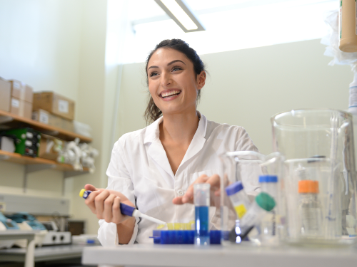 A women smiling in a scientific lab using a syringe